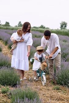 Eine junge familie geht mit ihren kindern über ein lavendelfeld.