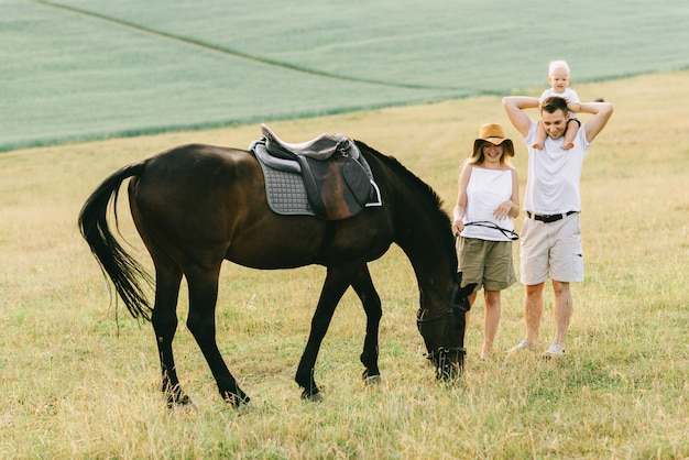 Eine junge familie hat spaß auf dem feld. eltern und kind mit einem pferd