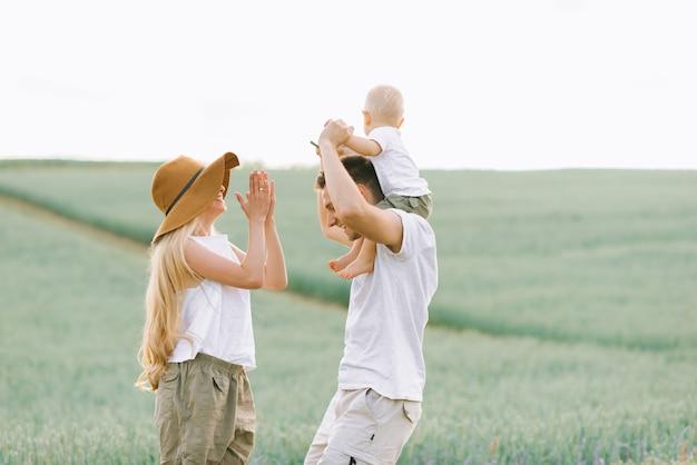 Eine junge familie hat spaß mit ihrem kleinen baby auf dem feld