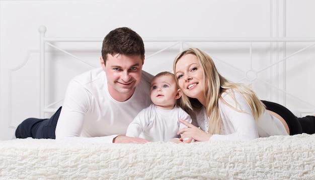 Eine junge familie mit einem baby auf dem bett liegend
