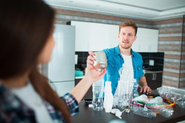Eine junge familie sortiert materialien in der küche zum recycling. recycelbare materialien müssen getrennt werden. die frau gibt ihrem mann eine alte blechdose für lebensmittel. sie sortieren den ganzen müll im haus