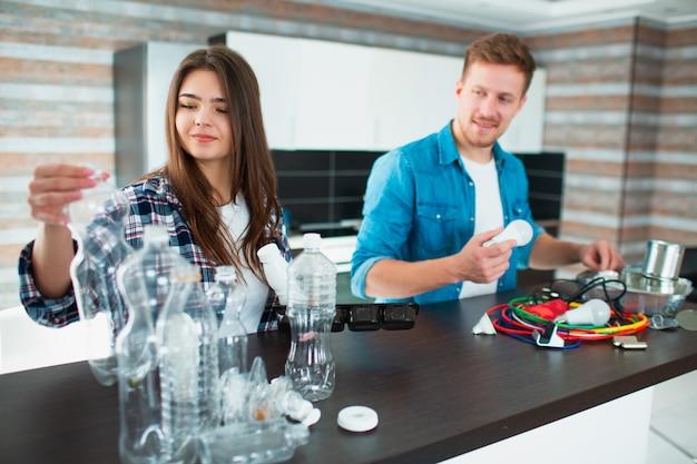 Eine junge familie sortiert materialien in der küche zum recycling. recycelbare materialien müssen getrennt werden. frau sortiert plastik und ehemann sortiert alte elektrogeräte, eisenglas und anderen müll, abfall