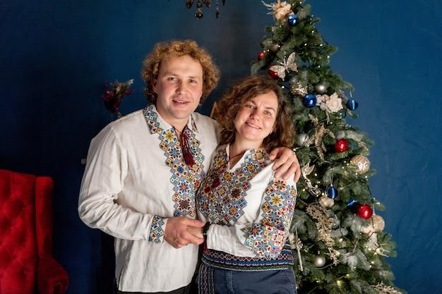 Eine junge familie steht am weihnachtsbaum