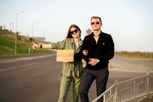 Eine junge familie von anhängern auf der autobahn, die auf das auto wartet, reist mit liebe in die freiheit