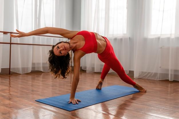 Eine junge fitnesstrainerin in roten sportswear-leggings und top-stretching im fitnessstudio vor ihr before