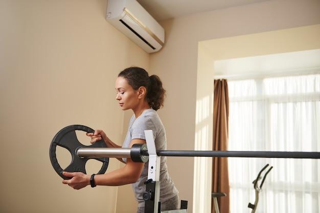 Eine junge, fitte frau legt während des bodybuilding-trainings eine metallscheibe auf eine olympische langhantel