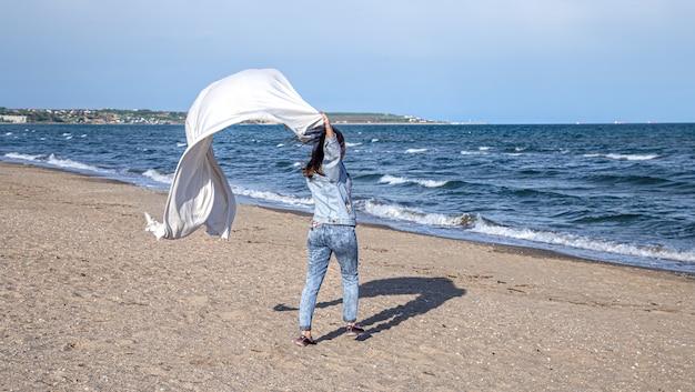 Eine junge frau am meer hat spaß daran, ein großes laken im wind zu halten, ein freier lebensstil.