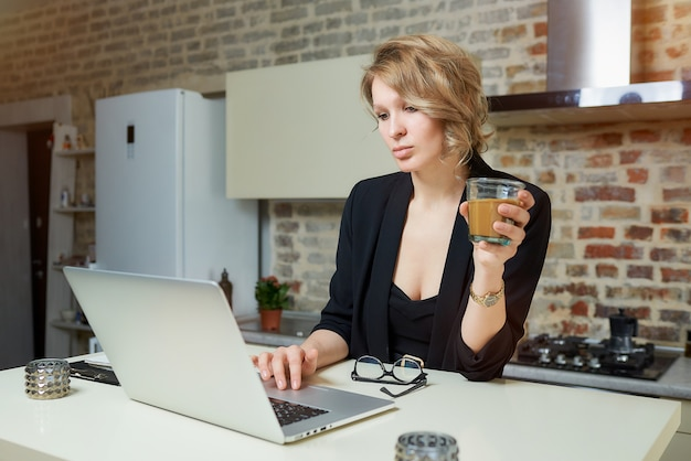 Eine junge frau arbeitet in ihrer küche an einem laptop. eine dame hält ein glas kaffee in der hand und bereitet sich auf einen vortrag bei einem videoanruf vor.