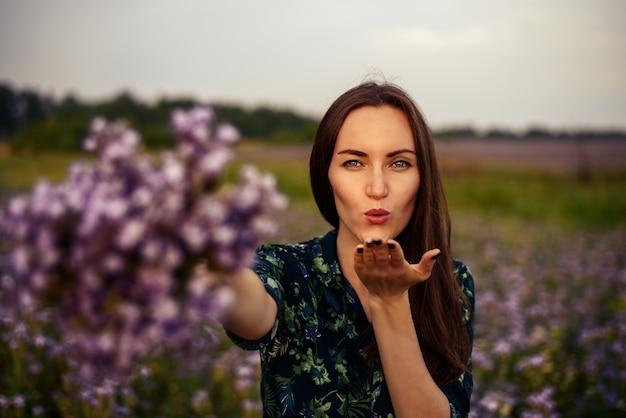 Eine junge frau auf dem feld streckt einen blumenstrauß und schickt einen kuss an die kamera