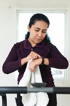 Eine junge frau auf dem laufband, die im fitnessstudio auf ihre uhr schaut, während sie ein handtuch hält