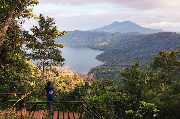 Eine junge frau auf einer holzbrücke, die einen schönen blick auf den mombacho-vulkan und die apoyo-lagune schätzt