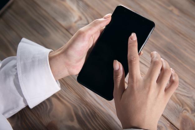 Eine junge frau benutzt ihr smartphone an einem tisch