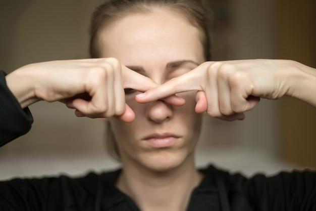 Eine junge frau berührt ihre nase, weil sie ihren geruchssinn verliert und den geruch nicht spürt. anosmia