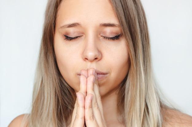 Eine junge frau betet mit geschlossenen augen und gefalteten händen, dankt den wunsch, um hilfe zu hoffen