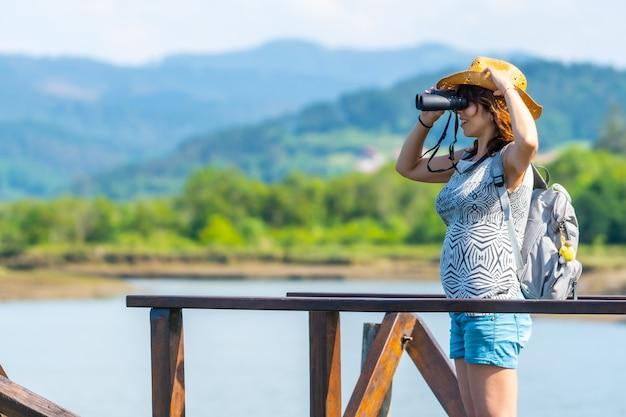 Eine junge frau betrachtet die vögel von den holzstegen des urdaibai-sumpfes, einem biosphärenreservat in bizkaia neben mundaka. baskenland