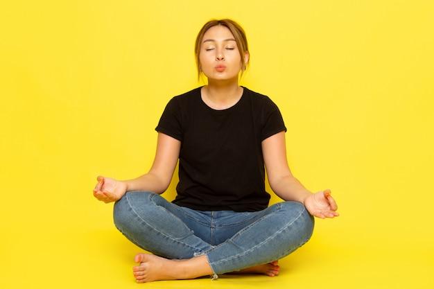 Eine junge frau der vorderansicht, die im schwarzen hemd und in den blauen jeans sitzt, die über gelb meditieren
