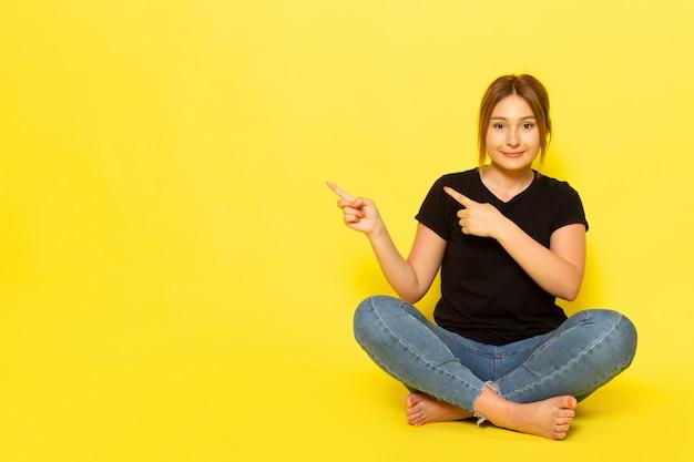 Eine junge frau der vorderansicht, die im schwarzen hemd und in den blauen jeans sitzt und mit lächeln auf gelb aufzeigt