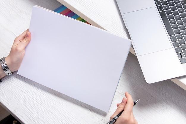 Eine junge frau der vorderansicht, die mit leeren rohlingen vor tisch mit laptops jobaktivitätsgeschäft arbeitet