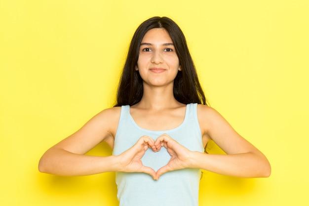 Eine junge frau der vorderansicht im blauen hemd, das herzzeichen auf dem gelben hintergrundmädchen darstellt modell pose schönheit jung aufwirft und zeigt