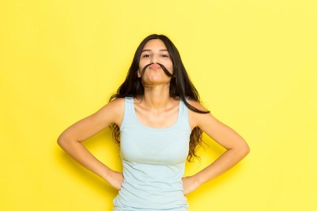 Eine junge frau der vorderansicht im blauen hemd, das mit ihren haaren als schnurrbart aufwirft