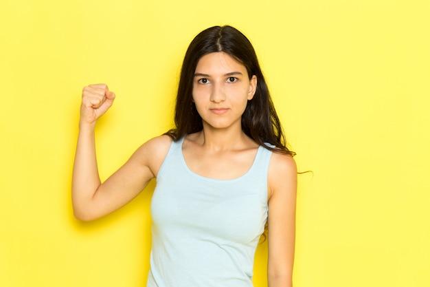 Eine junge frau der vorderansicht im blauen hemd, das mit wütendem ausdruck und knöchel auf dem gelben hintergrundmädchen posiert, modelliert modellschönheit jung