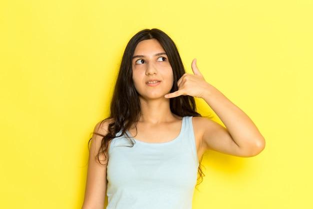 Eine junge frau der vorderansicht im blauen hemd, das telefonanrufzeichen auf dem gelben hintergrundmädchen darstellt, stellt modellschönheit jung dar