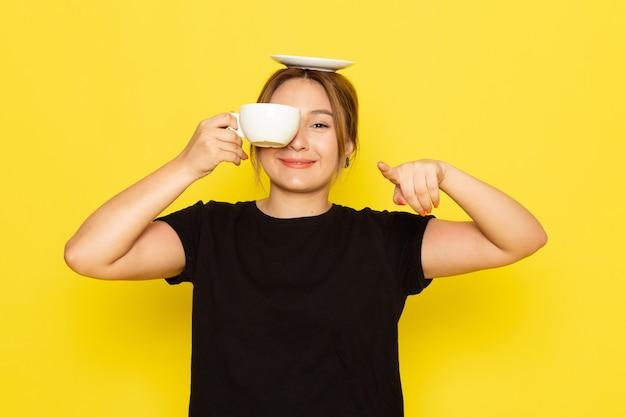Eine junge frau der vorderansicht im schwarzen kleid, das kaffee trinkt und auf gelb lächelt