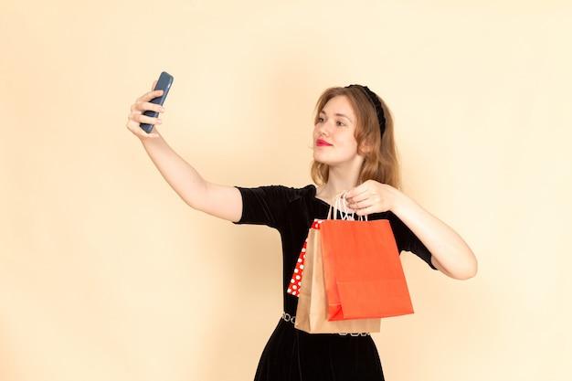 Eine junge frau der vorderansicht im schwarzen kleid mit kettengürtel, der einkaufspakete hält und ein selfie auf beige nimmt