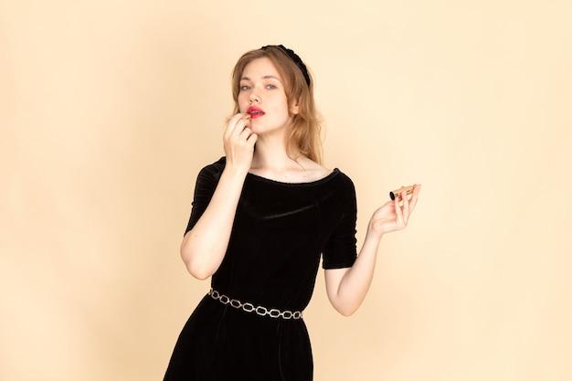 Eine junge frau der vorderansicht im schwarzen kleid mit kettengürtel, der make-up auf beige tut