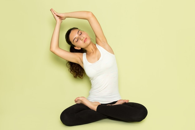 Eine junge frau der vorderansicht im weißen hemd und in den schwarzen hosen, die sitzend in der meditierenden yoga-pose auf dem grünen hintergrundmädchen-posenmodellschönheits-jungen emotionssportyoga darstellen