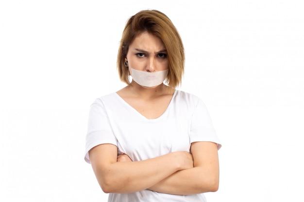 Eine junge frau der vorderansicht im weißen t-shirt, das weißen verband um ihren mund trägt, missfiel auf dem weiß