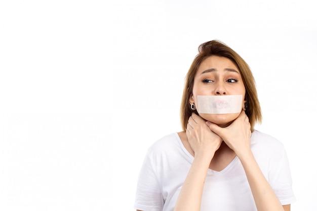 Eine junge frau der vorderansicht im weißen t-shirt mit weißem verband um ihren mund, der auf dem weiß erstickt wird