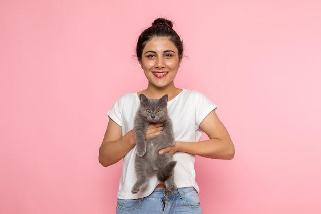Eine junge frau der vorderansicht im weißen t-shirt und in den blauen jeans, die graues kätzchen halten