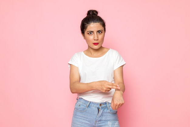 Eine junge frau der vorderansicht im weißen t-shirt und in den blauen jeans, die in ihr handgelenk zeigen