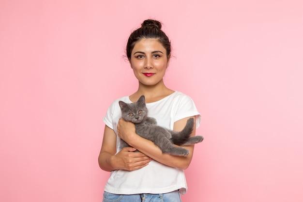 Eine junge frau der vorderansicht im weißen t-shirt und in den blauen jeans, die niedliches graues kätzchen mit lächeln halten