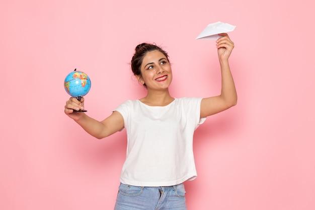 Eine junge frau der vorderansicht im weißen t-shirt und in den blauen jeans, die papierflugzeug und kleinen globus halten
