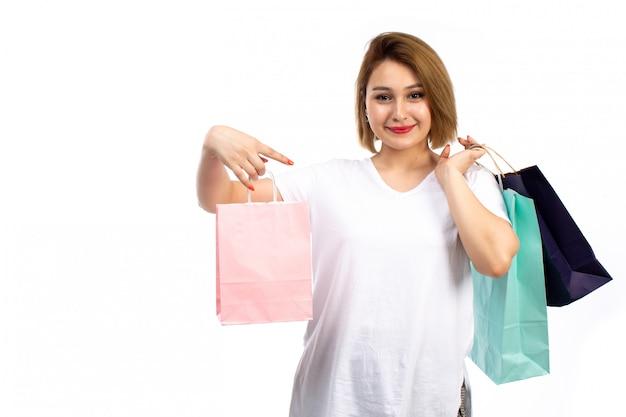 Eine junge frau der vorderansicht im weißen t-shirt und in den schwarzen jeans, die verschiedenfarbige einkaufspakete halten, die auf dem weiß lächeln
