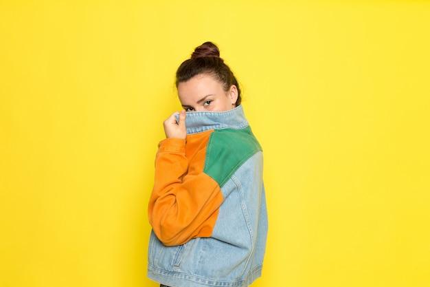 Eine junge frau der vorderansicht in der bunten jacke des gelben hemdes und in den blauen jeans, die aufwerfen