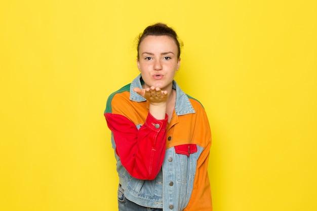 Eine junge frau der vorderansicht in der bunten jacke des gelben hemdes und in den blauen jeans, die luftküsse aufwerfen und senden