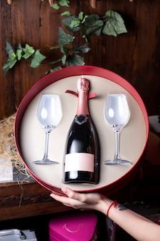 Eine junge frau der vorderansichtflasche, die runde schachtel mit flasche rotwein und mit zwei gläsern auf dem braunen schreibtischalkohol-weingut-getränk hält