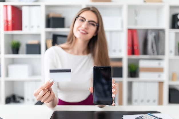 Eine junge frau, die an einem tisch sitzt und ein telefon und eine kreditkarte hält. foto mit schärfentiefe, hervorgehobener fokus auf karte und telefon.