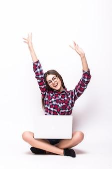 Eine junge frau, die auf dem boden mit einem laptop auf weiß sitzt
