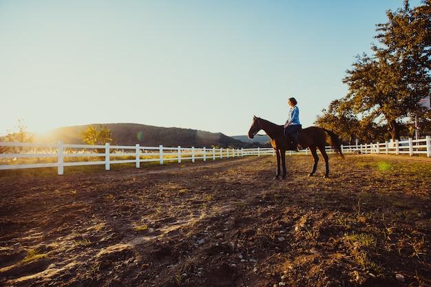 Eine junge frau, die auf einem pferd reitet, betrachtet den sonnenuntergang