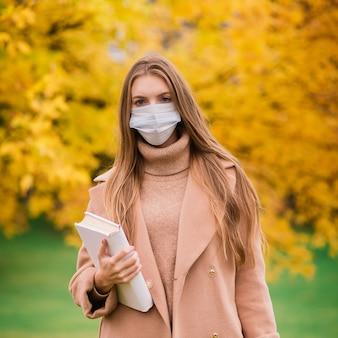 Eine junge frau, die beim gehen im park vor dem koronavirus schützt