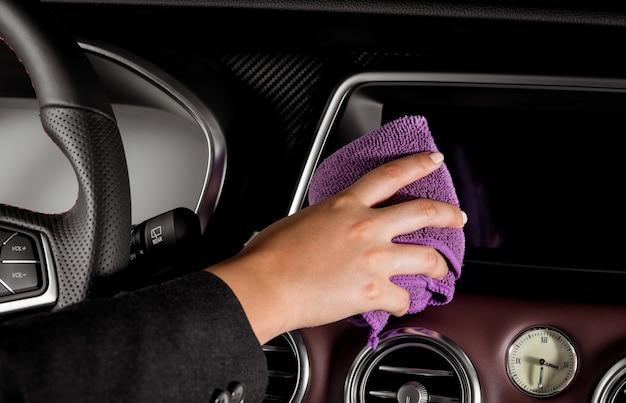 Eine junge frau, die den bildschirm in einem luxuriösen auto reinigt