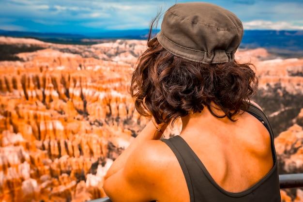 Eine junge frau, die den canyon von bryce point im bryce national park betrachtet. utah, vereinigte staaten