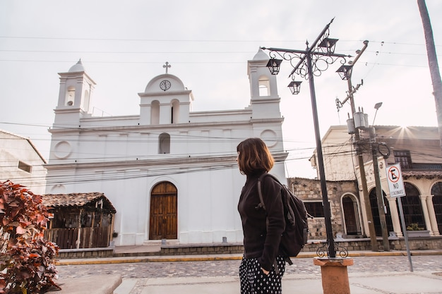 Eine junge frau, die die weiße kirche in der stadt copan ruinas in honduras betrachtet