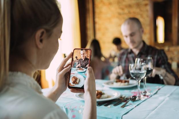 Eine junge frau, die ein foto ihres partners mit ihrem smartphone in einem restaurant macht.