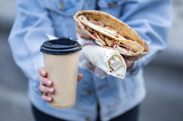 Eine junge frau, die ein glas kaffee und fast food hält.