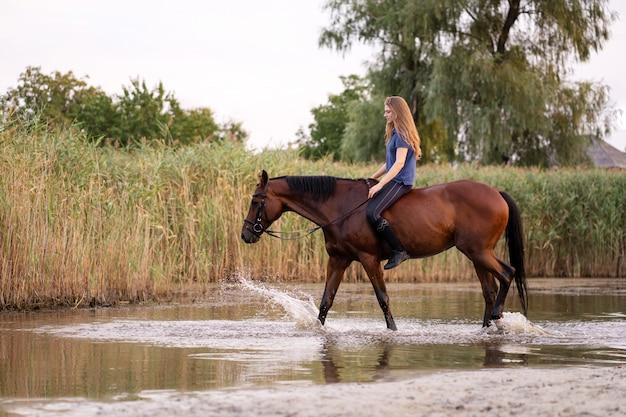 Eine junge frau, die ein pferd auf einen flachen see reitet. ein pferd läuft auf dem wasser bei sonnenuntergang. kümmere dich um das pferd und gehe mit ihm. kraft und schönheit